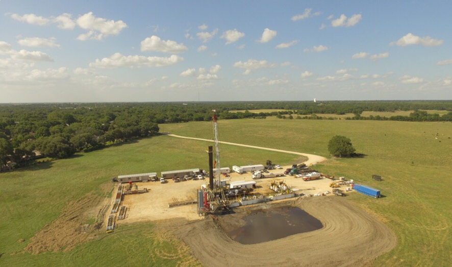 COG1 drilling rig showing oil overflow pit in foreground